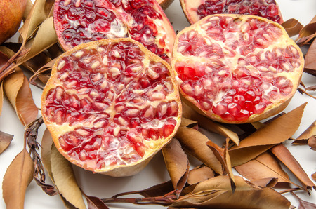 Fresh Pomegranates on background of autumn leaves photo