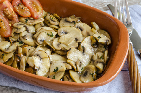 kitchen spanish: Uncooked sliced mushrooms with tomatoes in ceramic baking form