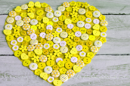 yellow heart: Yellow heart covered with colorful buttons.Valentines day. From above Stock Photo