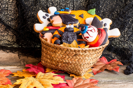 Wattled basket full of halloween homemade cookies on autumnal foliage