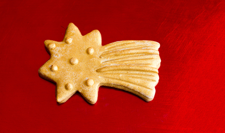 red metal background: Close-up of gold Christmas star cookie on red metal background