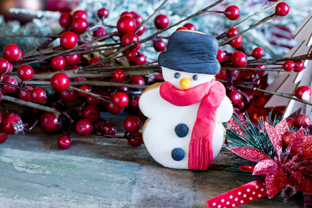Close-up of butter cookie in shape of snowman against of berry branch on table Stock Photo