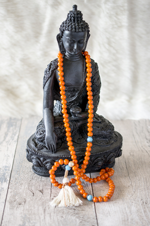 buddah: portrait of black buddah statue with orange religion beads hanging on neck. Stock Photo