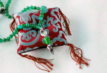 utterance: close-up of beautiful glass beads of green color on red and blue decorative pillow on white background