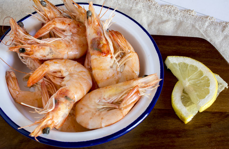 langoustine: Close up of cooked shrimps with slices of lemon in blue plate on wooden desk Stock Photo