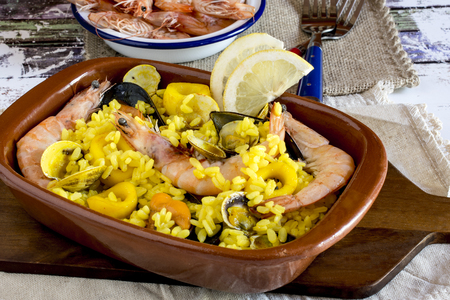 Close up of cooked shrimps with yellow rice and vegetables and oisters with slices of lemon in brown plate on wooden desk