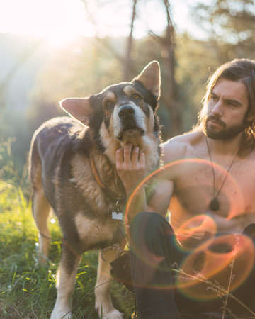 Portrait of a bearded man with his old dog and a beautiful sunset on the mountain