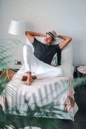 Ethnic stylish young man with a hat looking to the side and smiling lying on a sofa in a minimalism house