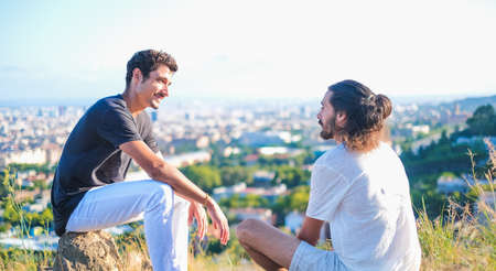 Ethnic and caucasian young mans looking each other in a profound way having a good conversation while sitting in the nature with a city on the background