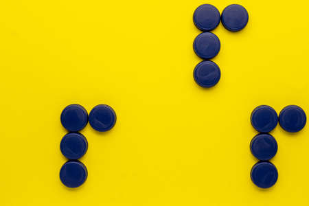 Concept of the three R's: recycle, reuse, reduce. Plastic bottle caps on a yellow background