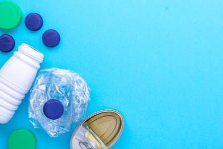 Recycling garbage. White plastic bottle, green cap, blue caps, can of sardines grouped on the left side diagonal on a blue background. Stock Photo