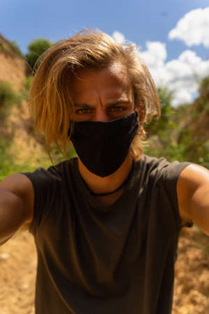Self portrait of young man with medium long blond hair and blue eyes with mask in his mouth from the virus in the middle of the forest and nature Imagens