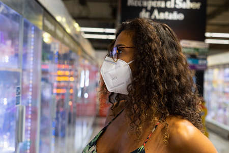 Brazilian young woman shopping in the supermarket with mask. New normality concept.