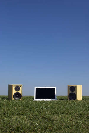 Royalty Free Stock Image of a photograph of a laptop on grass against a clear blue sky providing copy space above with a pair of speakers in a conceptual manner photo