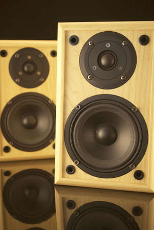 free stock: Royalty free stock image of a pair of speakers with a warm glow, against black and on a black reflective surface Stock Photo
