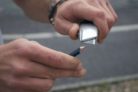 free stock: A royalty free stock image of a worker using his knife to sharpen his pencil, taken close up