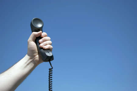 free stock: Royalty Free Stock Image of a male hand holding a black telephone receiver against a clear blue sky, lightly vignetted, with copy space