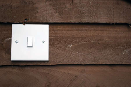 free stock: Royalty free stock image of white light switch against wood background with copyspace to the right