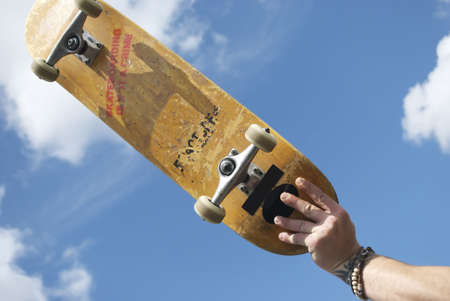 free stock: A royalty free stock image of a skateboarder holding their skateboard in the air against sky with the words skateboarding is not a crime on the underside of the board Stock Photo