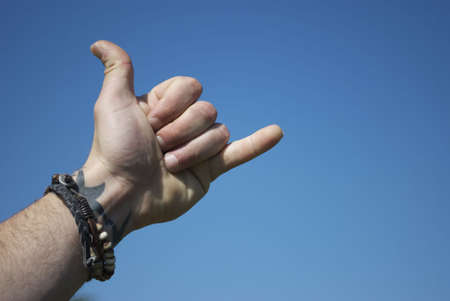 dedo me�ique: Libre de derechos de imagen de valores de una mano los hombres, en el saludo hawaiin, se�al relacionada surfista, contra un cielo azul claro con copia espacio a la derecha