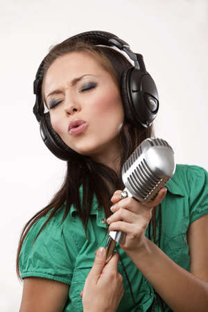 amazing beautiful girl with professional studio microphone and headphones on white background in studio shooting