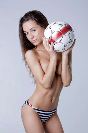 one beautiful girl in swimsuit at one studio shooting holding a soccer ball