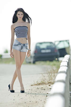 beautiful sexy girl in shorts jeans at outdoor shooting