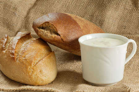 two breads with a cup of sour cream on a canvas bag Stock Photo