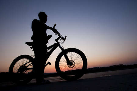 a cyclist listen music on city background at the sunset Stock Photo