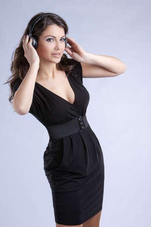 amazing beautiful girl with headphones in black dress at studio shooting Stock Photo
