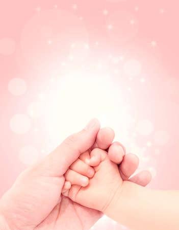 キラキラ背景に愛の手をつないで赤ちゃん