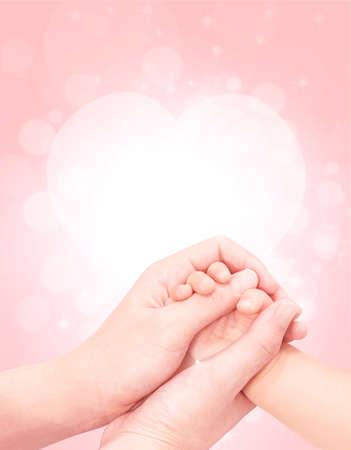 ピンクのキラキラ バック グラウンドでそっと母の手で赤ちゃんの手