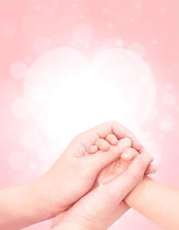 baby hand in mother hand softly with pink glitter background