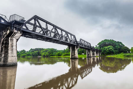 railway history: Railway Bridge of world war history in the rain cloud, River Kwai, Kanchanaburi, Thailand