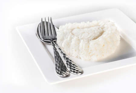 thai culture: jasmine rice on dish with spoon and fork, ready to eat