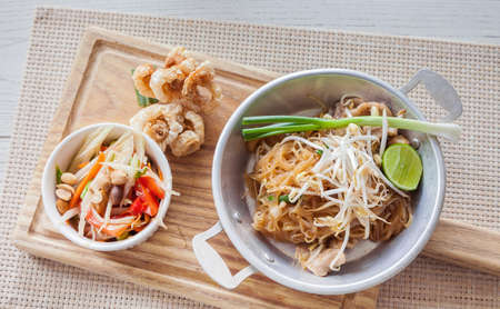 crackling: Thai food, fried noodles Thai style with papaya salad and pork crackling, name in Thai is Phat Thai and Somtum