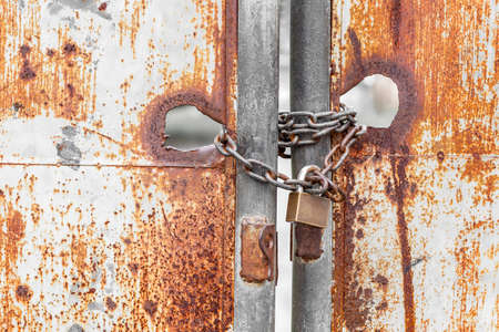 Vintage rusty gate with locked master key and metal chain Stock Photo