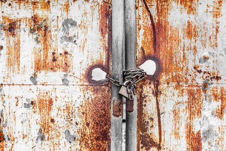 master key: Vintage rusty gate with locked master key and metal chain Stock Photo