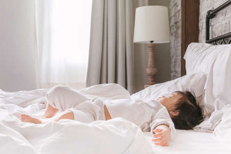 nighty: young baby 2-3 year sleeping on the bed in morning sunrise, sleepy and lazy girl in the bedroom, sleeping child Stock Photo