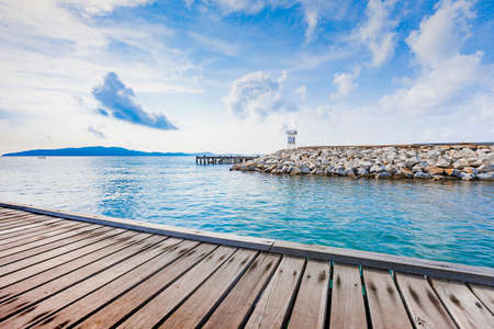 Wooden plank pier with seascape and bright blue sky for relax time at Khao Leam Ya National Park, Rayong Province, Thailand