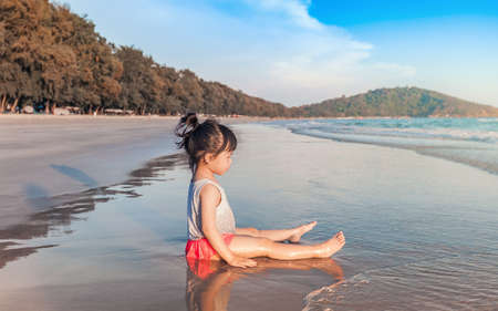 joyfully: little asian girl 2-3 years sit and plays on the beach in summer time sunset Stock Photo