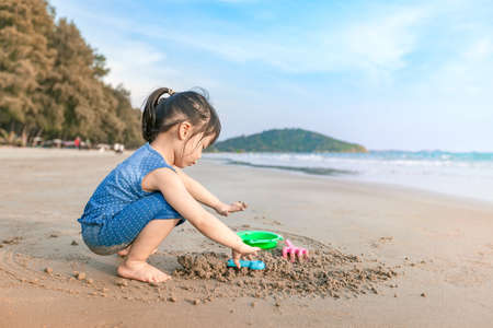 little asian girl 2-3 years sit and plays with imagination on the beach in summer time sunset
