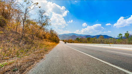 On the way in highway to countryside with bright blue sky and nature mountain landscape