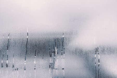 Regendruppels op glazen raam in het regenseizoen met monotone