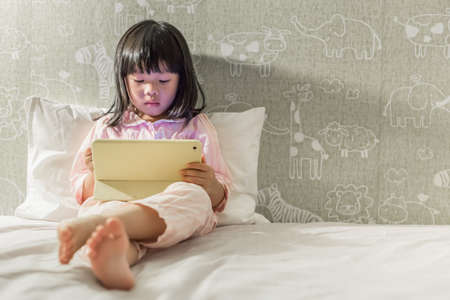young asian little girl 4-6 years in pyjamas playing tablet on the bed before bedtime Reklamní fotografie