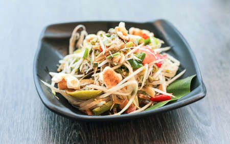 Papaya salad, Thai traditional food or name in Thai Somtum, papaya in fermented fish sauce with vegetable and pork cracklings in black dish on wooden table Stock Photo