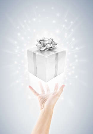 giving or carrying hand with silver celebrate gift box and magic twinkles