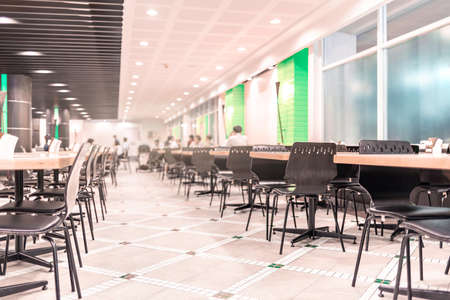 Modern interior of cafeteria or canteen with chairs and tables, eating room in selective focus Imagens