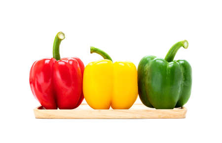 fresh vegetable bell peppers in three colored red, green, yellow in wooden plate isolated on white background