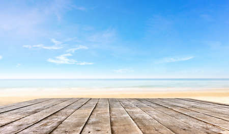 wooden table top or wooden plank in front of the beach background for products or object display
